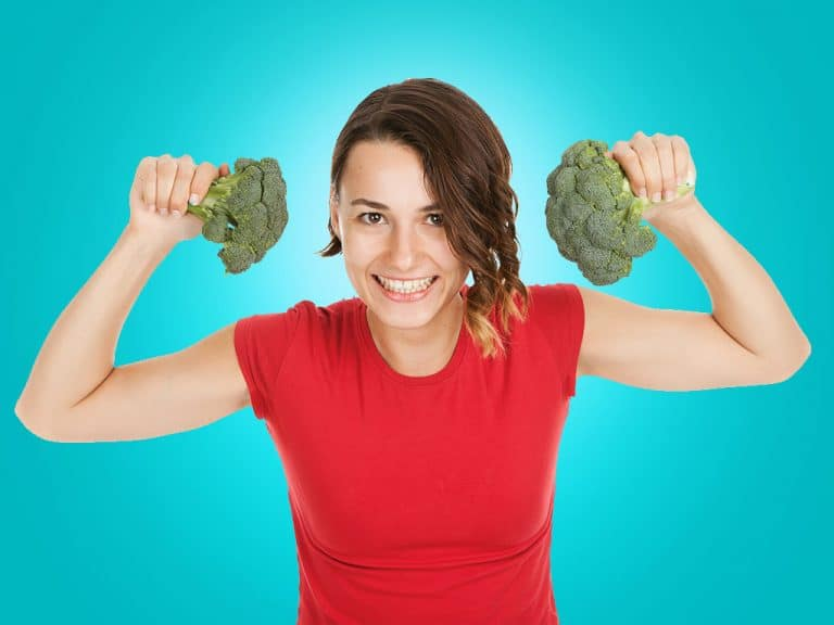 plants to start now: young woman holding broccoli in her hands